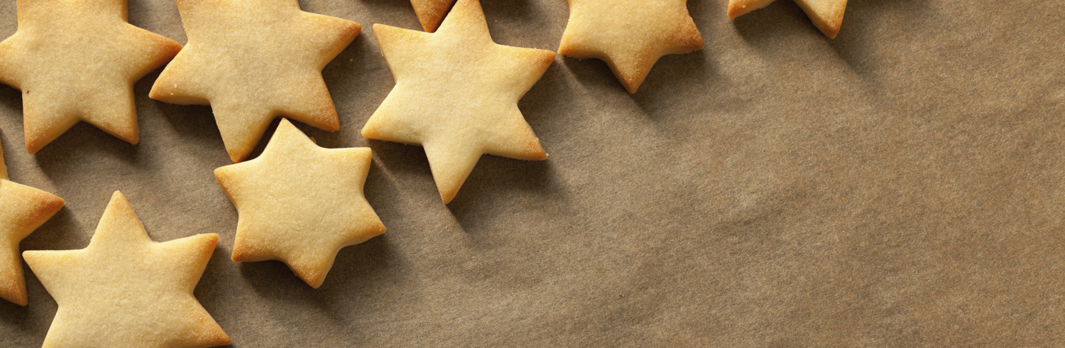 christmas biscuit stars on baking sheet with place for text